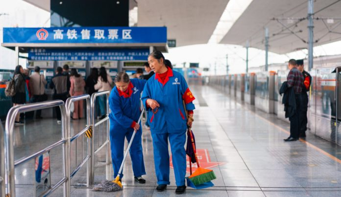 Cleaning staff working on a platform at Chengdu train station in China.