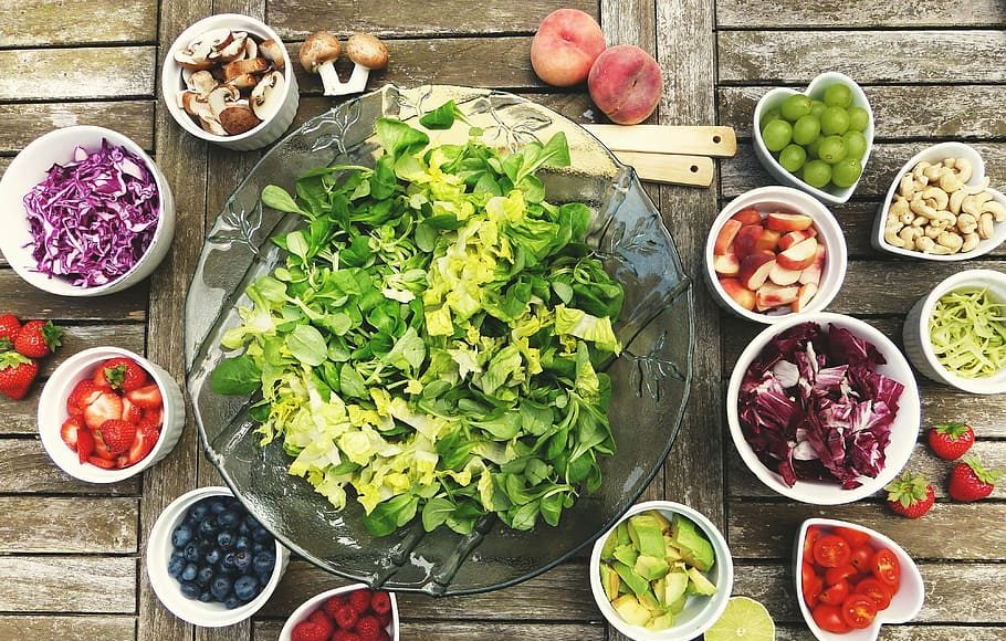 Prevent Chronic disease by adding more healthy food to your diet like a large glass bowl of green salad, surrounded by smaller bowls of different fruits, nuts, and vegetables,  on top of a wooden plank table.