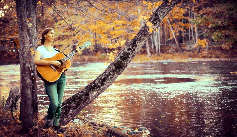 Katy Mantyk singing and playing guitar by a river.